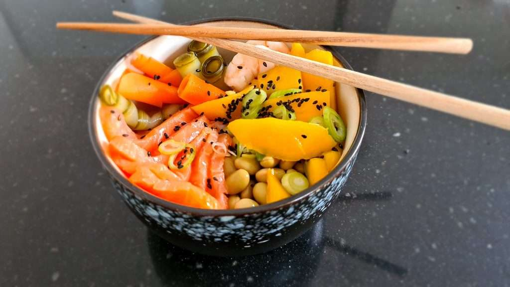 Poké bowl met zalm, garnalen en gember soja dressing en ingelegde groenten